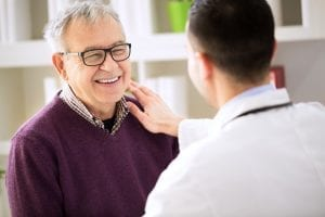 doctor with older male patient smiling
