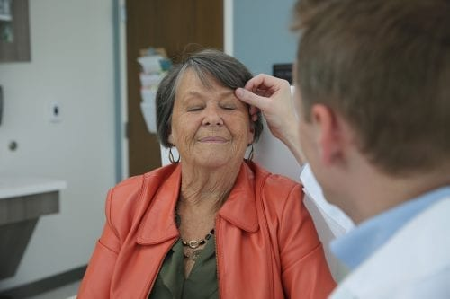 dermatologists inspects face of female patient